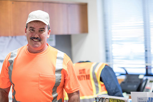 A male ORISE facilities employee wearing high visibility clothing