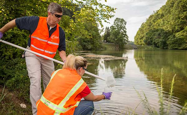 ORISE survey technicians collect a water sample