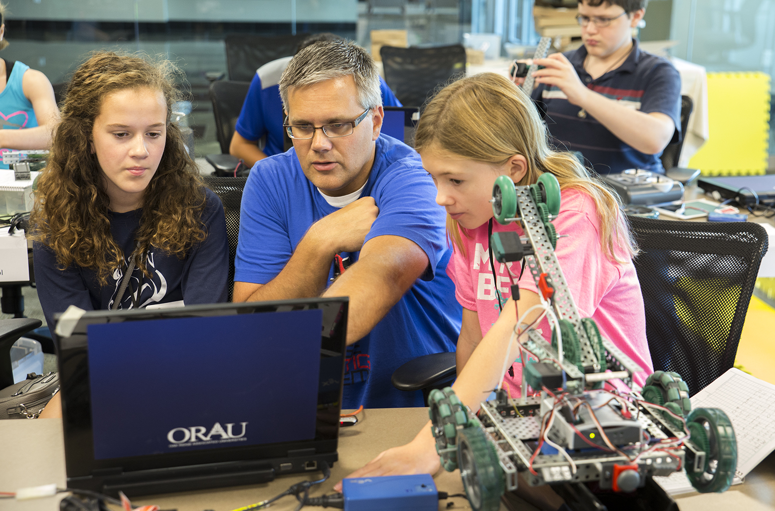A teacher helps two students with coding during the Oak Ridge Robotics Academy